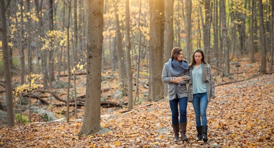 Image of mother & daughter walking in the forest